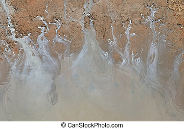 Polluted water - Oil trickle down from sandy riverside into...