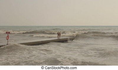 Young Romantic Pair on the Pier During Stormy Sea