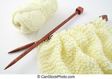 Knitting wool - Cream coloured, knitted wool on wooden...
