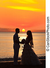 Sunrise wedding - Shape of a bride and groom on the beach at...