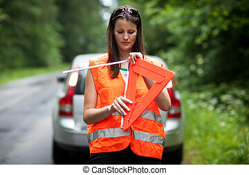 female driver with warning triangle - Young female driver...