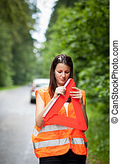 female driver with warning triangle