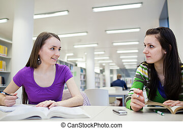 in the library - two female students with books working in a...