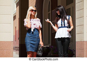 Two young women walking on a city street
