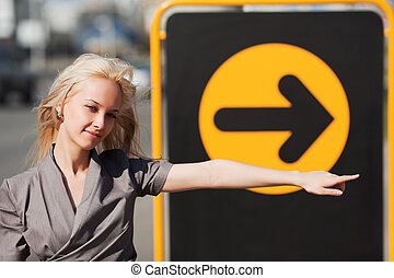 Direction sign - Young woman pointing a direction