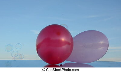 two balloons on mirror and bubbles