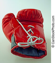 Glove - Single red and black boxe glove laying over gray...