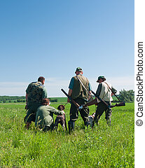 hunters - group of hunters with their dogs looking into the...
