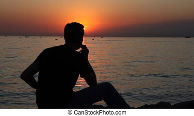 smoking cigarette - man smoking cigarette at the sunset