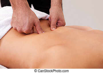 Young beautiful woman getting back massage. Spa studio shot