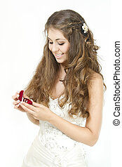 Bride holding red heart shaped box with two golden wedding rings. Smiling and looking at rings. Over white
