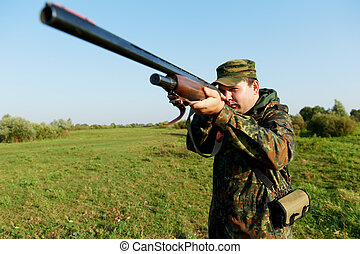 hunter with rifle gun - Male hunter in camouflage clothes on...