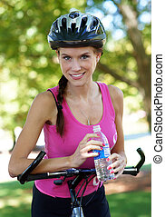 Water Break - Woman takes a rest from a bike ride and has a...