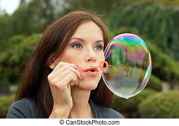 Bubble Blower - Woman blowing bubbles in the park