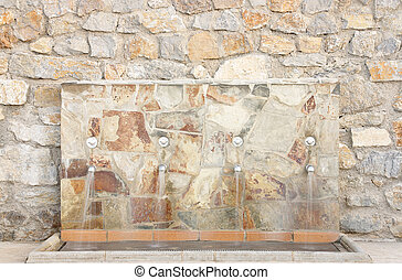 Water source in wall of stone - Water source the feet to be...