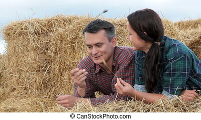 Togetherness - Young happy couple relaxing on haystack