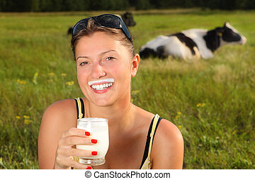 Fresh milk - A picture of a young happy woman drinking fresh...