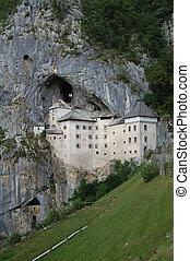 Predjama Castle (also known as Predjamski Grad) is a...