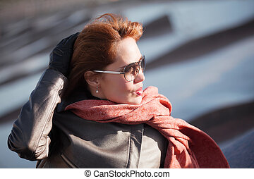 Woman in red scarf - Beautiful woman in red scarf on a city...