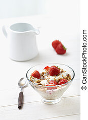 Milk with cereal and strawberries on a white table, country...