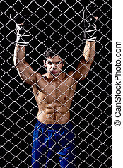Mixed martial artist posed behind chain link