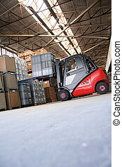Forklift in a big warehouse with palettes