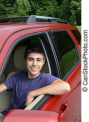 New teenage driver sits in his new car - A newly licensed...