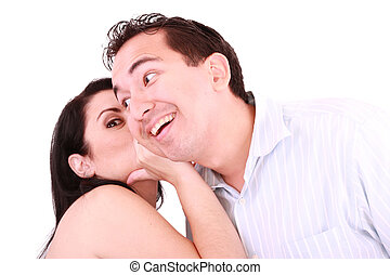 pretty girl talking secret to young man in his ear, man smiling over isolated white background