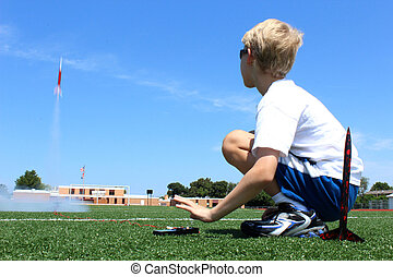 Boy Launches Rocket - A blond boy launches a model rocket on...