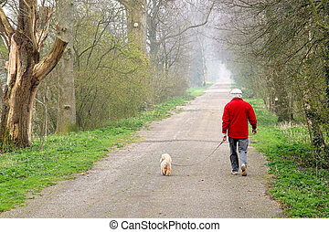 Man walking dog - Man walking his dog on a forest path
