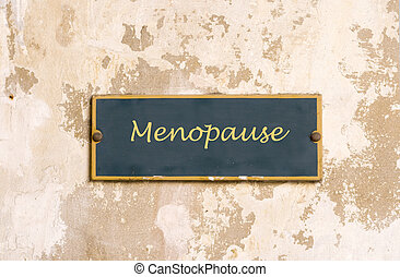 Menopause on weathered wall - Sign on medieval wall with...