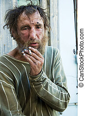 Homeless man smoking - Poor homeless beggar in depression