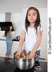 Girl mixing dough with mother in background