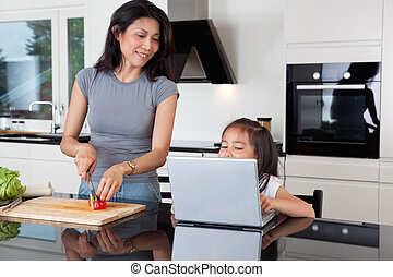 Mother and daughter with laptop in kitchen - Cute girl using...