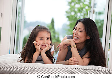 Mother and daughter on couch laughing - Portrait of mother...