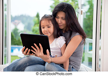 Mother and girl with E-book - Mother and girl holding E-book...