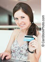 girl pays purchase through the Internet, sitting in cafe in...