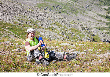 girl-tourist with a dark blue flask sits on the earth