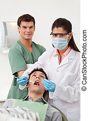 Patient having dental check up - Female dentist examining...