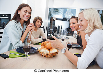 Smiling friends at dining table - Women showing something to...