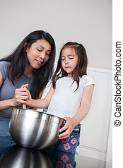 Mother and daughter in kitchen baking