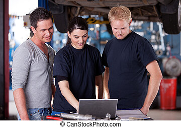 Mechanics with Laptop - A group of mechanics referring to a...