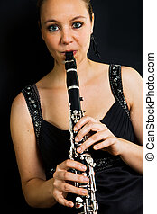 Young beautiful clarinetist playing Shot on black background...