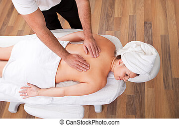 Young beautiful woman getting back massage