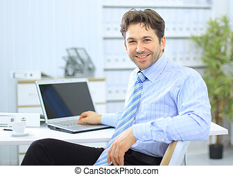 Businessman sitting at office desk working on laptop...