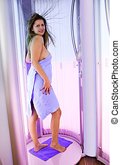 Beautiful young woman in vertical solarium