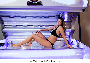 Young woman posing on tanning bed