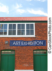 Art exhibition sign with brick building