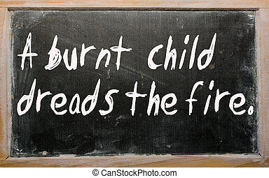 """""""A burnt  child dreads the fire"""" written on a blackboard"""