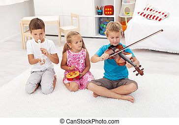 Kids trying to play on different musical instruments sitting...
